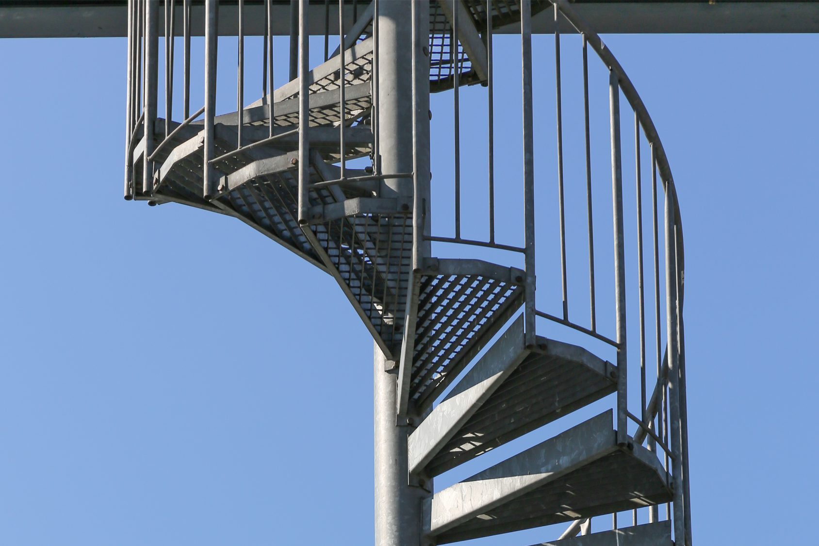 Steel circular staircase bright blue sky backdrop