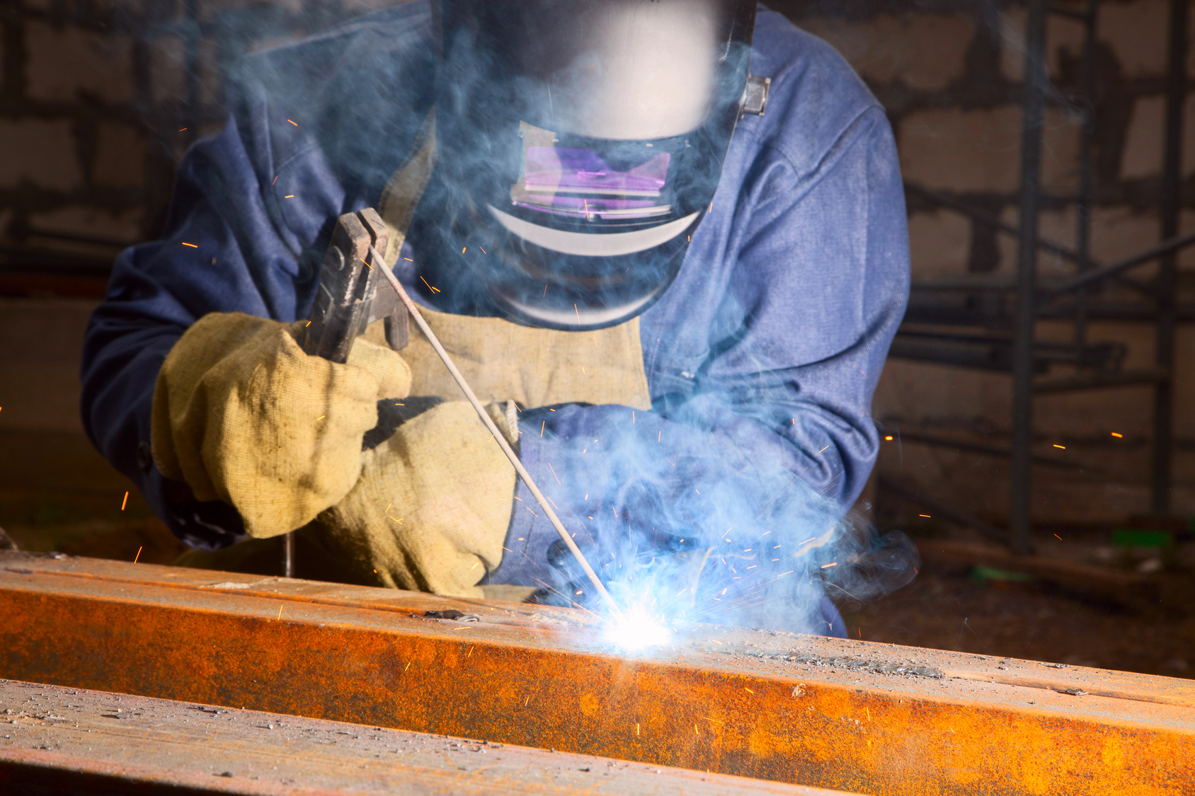 Worker weld metal at a construction site